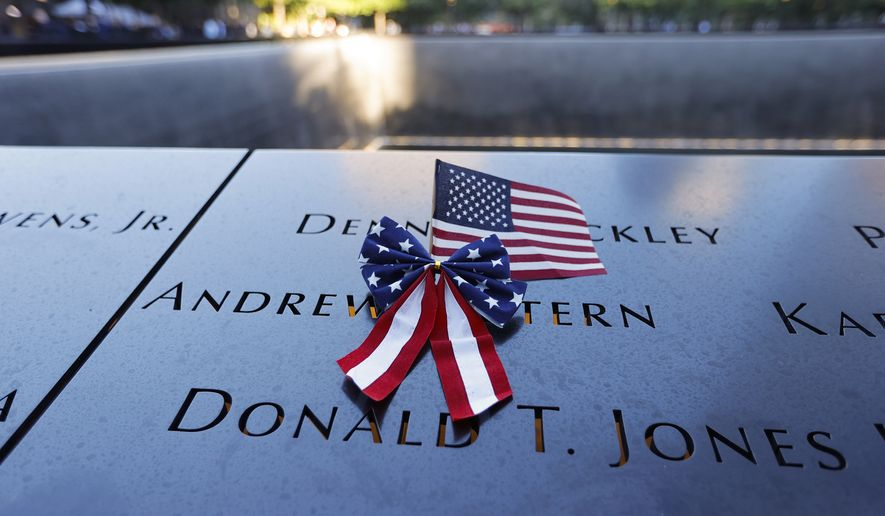 An American flag is seen on the National September 11 Memorial in New York on the 20th anniversary of the terrorist attacks, Saturday, Sept. 11, 2021. (Mike Segar/Pool Photo via AP)