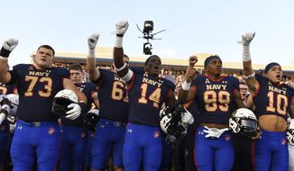 """Navy players raise their fists after singing """"Navy Blue and Gold"""" after an NCAA college football game against Air Force, Saturday, Sept. 11, 2021, in Annapolis, Md. (AP Photo/Terrance Williams) ** FILE**"""
