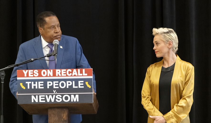 Former actor and activist Rose McGowan, right, listens to Republican conservative radio talk show host Larry Elder during a news conference at the Luxe Hotel Sunset Boulevard in Los Angeles, Sunday, Sept. 12, 2021. Elder is running to replace Democratic Gov. Gavin Newsom in the Sept. 14 recall election. McGowan was one of the earliest of dozens of women to accuse Hollywood producer Harvey Weinstein of sexual misconduct, making her a major figure in the #MeToo movement. (AP Photo/Damian Dovarganes)