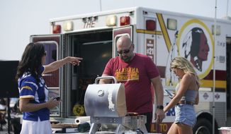 Branko Djurdjevic, from Rockville, Md., grilling in the parking lot at Fedex Field during tailgating before the start of an NFL football game between Los Angeles Chargers and Washington Football Team, Sunday, Sept. 12, 2021, in Landover, Md. (AP Photo/Al Drago)