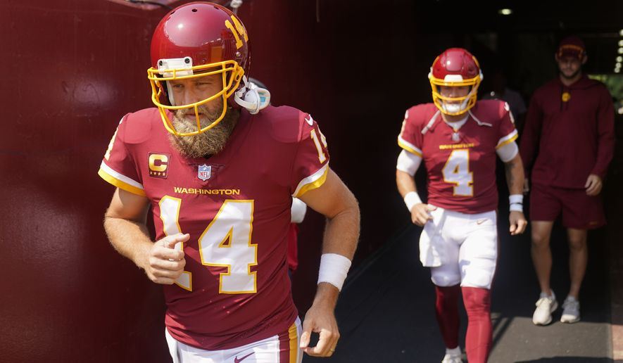 Washington Football Team quarterbacks Ryan Fitzpatrick (14) and Taylor Heinicke (4) take the field for warmups prior to the start of the first half of an NFL football game against the Los Angeles Chargers, Sunday, Sept. 12, 2021, in Landover, Md. (AP Photo/Andrew Harnik)