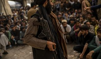 A Taliban fighter controls a crowd waiting to withdraw money from a bank branch in Kabul, Afghanistan, Sunday, Sept. 12, 2021. (AP Photo/Bernat Armangue) **FILE**
