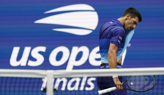 Novak Djokovic, of Serbia, wipes sweat from his face between serves from Daniil Medvedev, of Russia, during the men's singles final of the US Open tennis championships, Sunday, Sept. 12, 2021, in New York. (AP Photo/Elise Amendola)