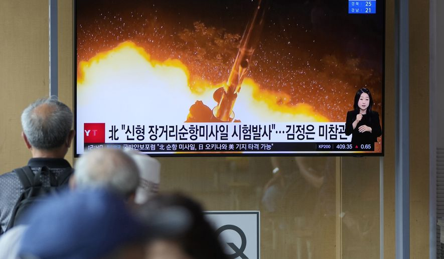 """People watch a news program that was showing part of a North Korean handout photo that says, """"North Korea's long-range cruise missiles tests,"""" in Seoul, South Korea, Monday, Sept. 13, 2021. North Korea says it successfully test-fired newly developed long-range cruise missiles over the weekend, its first known testing activity in months, underscoring how it continues to expand its military capabilities amid a stalemate in nuclear negotiations with the United States. The letters read, """"The North test-fired newly developed long-range cruise missiles."""" (AP Photo/Lee Jin-man)"""