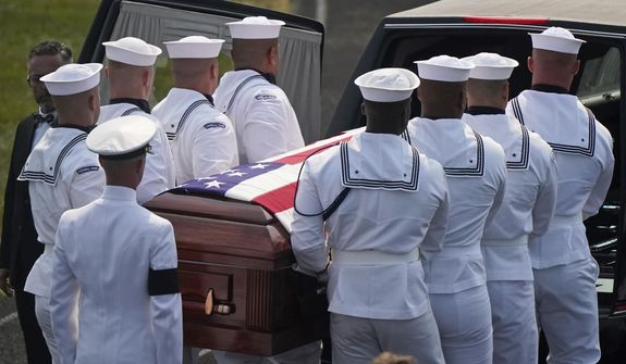 The body of Navy Corpsman Maxton Soviak is put into the hearse at Edison High School Stadium, Monday, Sept. 13, 2021, in Milan, Ohio. Soviak was one of 13 U.S. troops killed in a suicide bombing at Afghanistan's Kabul airport on Aug. 26. (AP Photo/Tony Dejak)