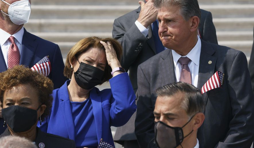 Sen. Amy Klobuchar, D-Minn., left, and Sen. Joe Manchin, D-W.Va., stand on the steps of the Capitol during a Sept. 11 remembrance ceremony, in Washington, Monday, Sept. 13, 2021. As congressional Democrats speed ahead this week in pursuit of President Joe Biden's $3.5 trillion plan for social and environmental spending, Manchin, a Democratic senator vital to the bill's fate, says the cost will need to be slashed to $1 trillion to $1.5 trillion to win his support. (AP Photo/J. Scott Applewhite) **FILE**