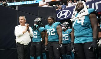 Jacksonville Jaguars coach Urban Meyer, left, prepares to lead his team onto the field before an NFL football game against the Houston Texans Sunday, Sept. 12, 2021, in Houston. (AP Photo/Sam Craft) **FILE**
