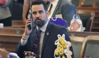 In this file photo from Monday, May 3, 2021, Kansas state Rep. Mark Samsel, R-Wellsville, talks on his cellphone ahead of the House's daily session, at the Statehouse in Topeka, Kan. Samsel, accused of kicking a high school student in the testicles pleaded guilty Monday, Sept. 13, 2021, to three lesser misdemeanor charges of disorderly conduct and was placed on a year's probation under an deal with the local prosecutor. (AP Photo/John Hanna File)