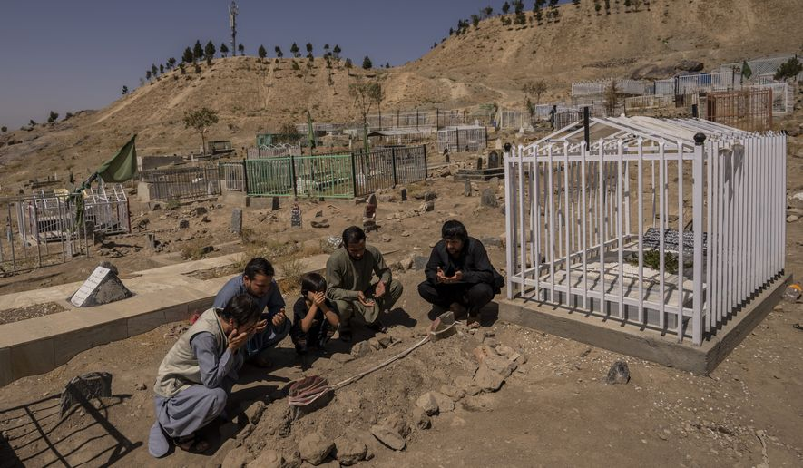 The Ahmadi family pray at the cemetery next to family graves of family members killed by a US drone strike, in Kabul, Afghanistan, Monday, Sept. 13, 2021. (AP Photo/Bernat Armangue)