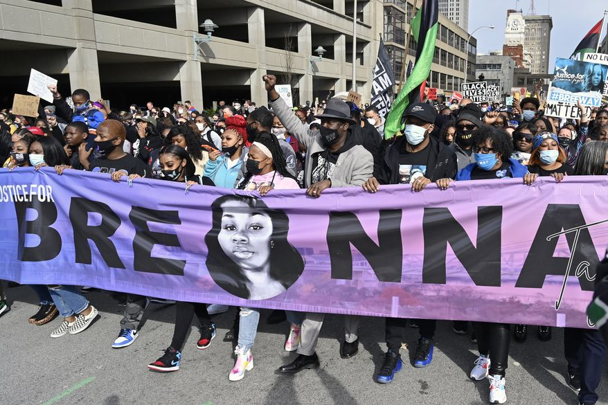 """In this March 13, 2021 file photo, Tamika Palmer, center, the mother of Breonna Taylor, leads a march through the streets of downtown Louisville on the one-year anniversary of her death in Louisville, Ky. The Justice Department said Tuesday, Sept. 14, it is curtailing federal agents' use of so-called """"no-knock"""" warrants — which allow law enforcement agents to enter a home without announcing their presence — and would also prohibit its agents from using chokeholds in most circumstances. The updated policy follows the March 2020 death of Breonna Taylor, who was shot and killed by police in her home during a no-knock warrant and whose death led to months of mass protests over racial injustice in policing and the treatment of Black people in the United States. (AP Photo/Timothy D. Easley, File)"""