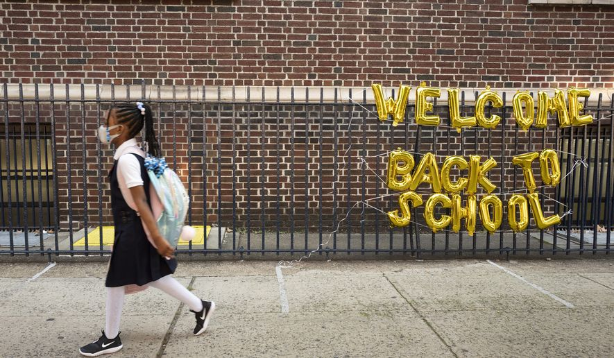 """In this Sept. 13, 2021, photo, a girl passes a """"Welcome Back to School"""" sign as she arrives for the first day of class at Brooklyn's PS 245 elementary school in New York. COVID-19 deaths and cases in the U.S. have climbed back to where they were over the winter, fueled by children now back in their classrooms, loose mask restrictions and low vaccination levels. (AP Photo/Mark Lennihan) **FILE**"""