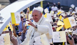 Pope Francis waves to faithful holding Vatican flags as he arrives on his pope-mobile to celebrate a Byzantine rite Mass at Mestska sportova hala Square, in Presov, Slovakia, Tuesday, Sept. 14, 2021. Pope Francis is on a four-day pilgrimage to Hungary and Slovakia. (AP Photo/Darko Vojinovic)