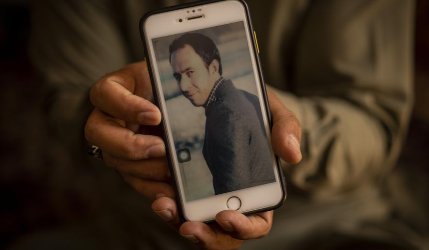 Amal Ahmadi, 32, holds a picture of his slain brother Zemerai Ahmadi at the family house in Kabul, Afghanistan, Monday, Sept. 13, 2021. Zemerai Ahmadi the Afghan man who was killed in a U.S. drone strike last month was an enthusiastic and beloved longtime employee at an American humanitarian organization, his colleagues say, painting a stark contrast to the Pentagon's claims that he was an Islamic State group militant about to carry out an attack on American troops. (AP Photo/Bernat Armangue)