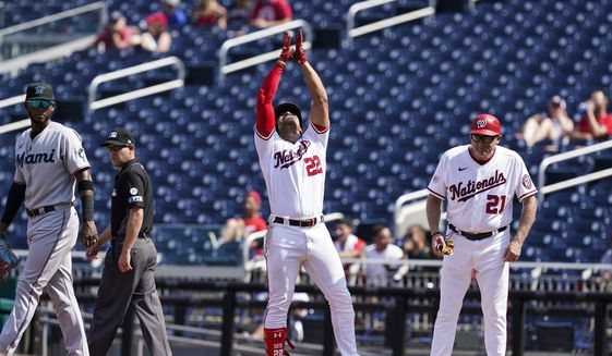 Washington Nationals' Juan Soto (22) celebrates his single alongside first base coach Randy Knorr during the third inning of a baseball game against the Miami Marlins at Nationals Park, Wednesday, Sept. 15, 2021, in Washington. (AP Photo/Alex Brandon)
