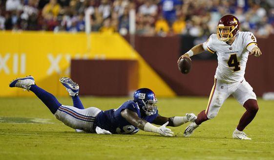 Washington Football Team quarterback Taylor Heinicke (4) scrambles away from New York Giants defensive end Leonard Williams (99) during the second half of an NFL football game, Thursday, Sept. 16, 2021, in Landover, Md. (AP Photo/Patrick Semansky)