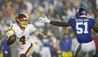 Washington Football Team quarterback Taylor Heinicke (4) runs to avoid being tackled by New York Giants linebacker Azeez Ojulari (51) during the first half of an NFL football game, Thursday, Sept. 16, 2021, in Landover, Md. (AP Photo/Patrick Semansky)