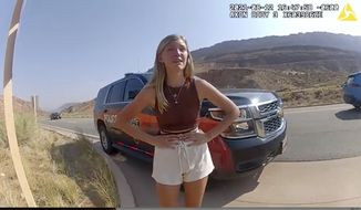 This police camera video provided by The Moab Police Department shows Gabrielle Gabby Petito talking to a police officer after police pulled over the van she was traveling in with her boyfriend, Brian Laundrie, near the entrance to Arches National Park on Aug. 12, 2021. The couple was pulled over while they were having an emotional fight. Petito was reported missing by her family a month later and is now the subject of a nationwide search. (The Moab Police Department via AP)
