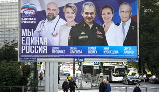 """People walk past an election poster in St. Petersburg, Russia, on Saturday, Sept. 11, 2021, ahead of the upcoming election for the State Duma, the lower house of the Russian parliament. The poster, from left, shows Denis Protsenko, head of the educational foundation """"Talent and Success""""; Yelena Shmeleva; Russian Defense Minister Sergei Shoigu; children's rights ombudsman Anna Kuznetsova; and Russian Foreign Minister Sergey Lavrov, candidates of the pro-Kremlin United Russia Party during the campaign. (AP Photo/Dmitri Lovetsky)"""
