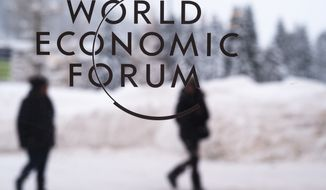 In this Sunday, Jan. 21, 2018, file photo, two people walk behind the logo of the World Economic Forum at the meeting's conference center in Davos, Switzerland. (AP Photo/Markus Schreiber, file)