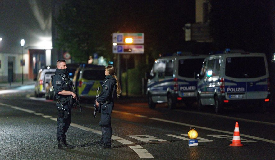 Police officers block a street in the city center during a police operation protecting the Jewish Community building in Hagen, Germany, Thursday, Sept. 16, 2021. Numerous police officers were involved in the operation, the police spoke of indications of a possible dangerous situation. (Henning Kaiser/dpa via AP)