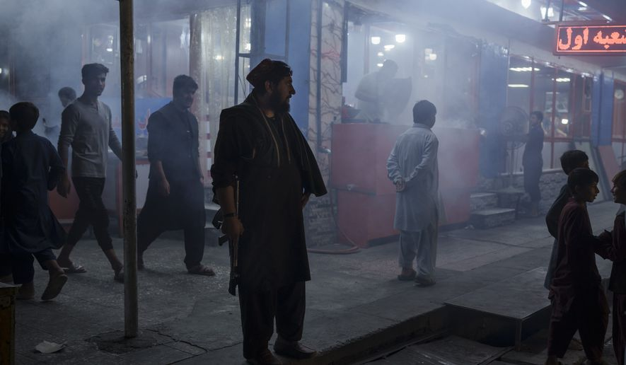 A Taliban fighter stands in the corner of a busy street at night in Kabul, Afghanistan, Friday, Sept. 17, 2021. (AP Photo/Felipe Dana)