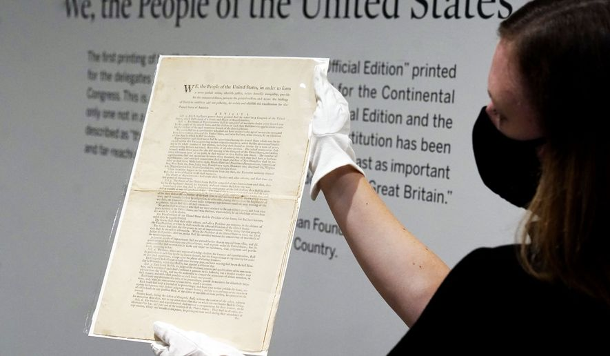 Ella Hall, a specialist in Books and Manuscripts at Sotheby's, in New York, holds a 1787 printed copy of the U.S. Constitution, Friday, Sept. 17, 2021. Sotheby's announced Friday — appropriately on Constitution Day — that in November it will put up for auction one of just 11 surviving copies of the Constitution from the official first printing produced for the delegates to the Constitutional Convention and for the Continental Congress. It's the only copy that remains in private hands and has an estimate of $15 million-$20 million. (AP Photo/Richard Drew)