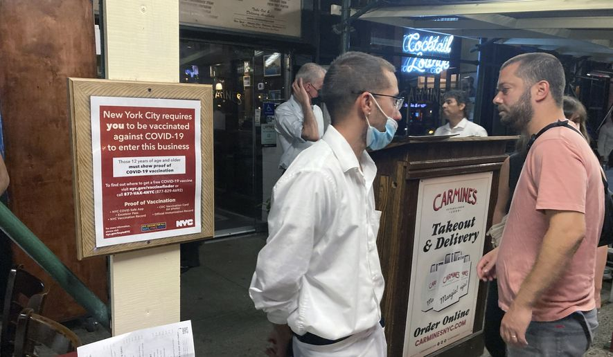 A sign informs customers they must show proof of vaccination against COVID-19 to dine indoors at Carmine's Italian restaurant on the Upper West Side of Manhattan in New York City on Tuesday, Aug. 31, 2021. (AP Photo/Ted Shaffrey) ** FILE **