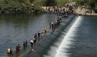 Haitian migrants use a dam to cross into the United States from Mexico, Saturday, Sept. 18, 2021, in Del Rio, Texas. The U.S. plans to speed up its efforts to expel Haitian migrants on flights to their Caribbean homeland, officials said Saturday as agents poured into the Texas border city where thousands of Haitians have gathered after suddenly crossing into the U.S. from Mexico. (AP Photo/Eric Gay)