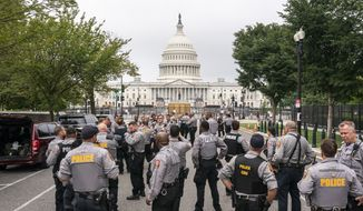 """Police stage at a security fence ahead of a rally near the U.S. Capitol in Washington, Saturday, Sept. 18, 2021. The rally was planned by allies of former President Donald Trump and aimed at supporting the so-called """"political prisoners"""" of the Jan. 6 storming of the U.S. Capitol. (AP Photo/Nathan Howard)  **FILE**"""