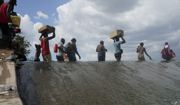 Haitian migrants use a dam to cross into and from the United States from Mexico, Saturday, Sept. 18, 2021, in Del Rio, Texas. The U.S. plans to speed up its efforts to expel Haitian migrants on flights to their Caribbean homeland, officials said Saturday as agents poured into a Texas border city where thousands of Haitians have gathered after suddenly crossing into the U.S. from Mexico. (AP Photo/Eric Gay)