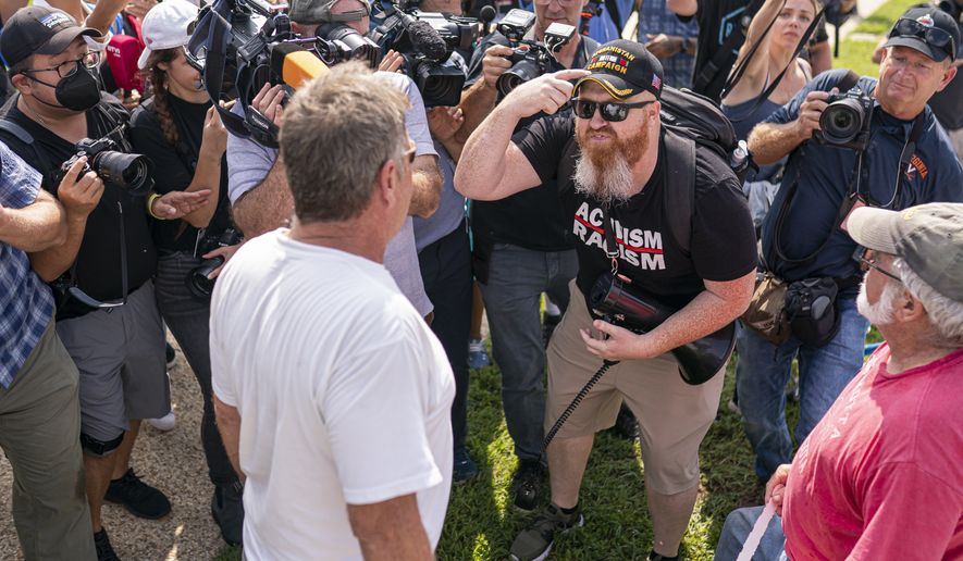 """A counter protester, right, argues with a Justice For J6 rally attendee near the U.S. Capitol in Washington, Saturday, Sept. 18, 2021. The rally was planned by allies of former President Donald Trump and aimed at supporting the so-called """"political prisoners"""" of the Jan. 6 insurrection at the U.S. Capitol. (AP Photo/Nathan Howard)"""