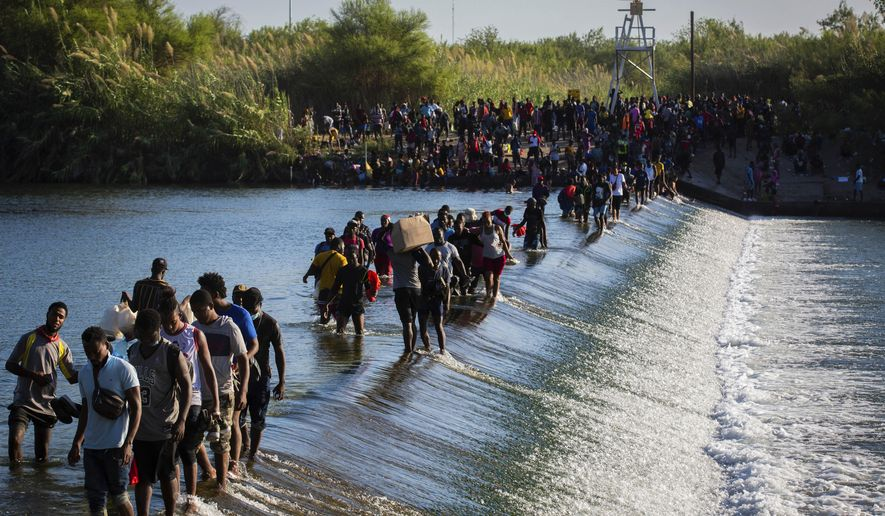 Haiti migrants waiting in Del Rio and Ciudad Acuña to get access to the United States, cross the Rio Grande toward Ciudad Acuña to get supplies, Friday, Sept. 17, 2021, in Ciudad Acuña, Mexico. Haitians crossed the Rio Grande freely and in a steady stream, going back and forth between the U.S. and Mexico through knee-deep water with some parents carrying small children on their shoulders. Unable to buy supplies in the U.S., they returned briefly to Mexico for food and cardboard to settle, temporarily at least, under or near the bridge in Del Rio, a city of 35,000 that has been severely strained by migrant flows in recent months. (Marie D. De Jesús/Houston Chronicle via AP)