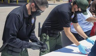 This May 4, 2021, photo provided by The U.S. Border Patrol shows U.S. Border Patrol Processing Coordinators help process and log personal items from migrants entering the Central Processing Center in El Paso, Texas. The Border Patrol says agents spend about 40% of their time on custody care and administrative tasks that are unrelated to border security, a staffing challenge that has come into focus with the arrival of thousands of Haitian migrants in the small Texas border city of Del Rio. (U.S. Border Patrol via AP)