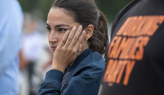 The rich person who designed Rep. Alexandria Ocasio-Cortez's slogan-wielding red-carpet gown is reportedly herself a tax deadbeat.. (AP Photo/Amanda Andrade-Rhoades)