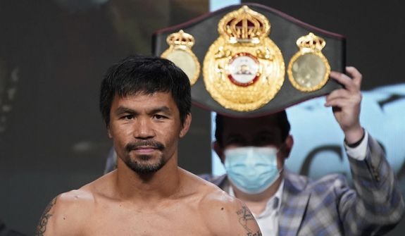 In this Aug. 20, 2021, file photo, Manny Pacquiao, of the Philippines, poses for photographers during a weigh-in in Las Vegas. Philippine boxing icon and senator Pacquiao says he will run for president in the 2022 elections. He accepted the nomination of his PDP-Laban party at its national convention on Sunday, Sept. 19, pledging to honestly serve the Filipino people who he said have been waiting for change in government. (AP Photo/John Locher, File)
