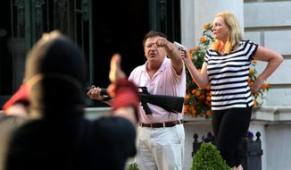 In this June 28, 2020, file photo, armed homeowners Mark and Patricia McCloskey, standing in front of their house along Portland Place, confront protesters marching to St. Louis Mayor Lyda Krewson's house in the Central West End of St. Louis. Missouri Chief Disciplinary Counsel Alan Pratzel is asking the state Supreme Court to suspend the law licenses of Mark and Patricia McCloskey, the St. Louis couple who gained national attention last year when they waved guns at racial injustice protesters outside their home. (Laurie Skrivan/St. Louis Post-Dispatch via AP)