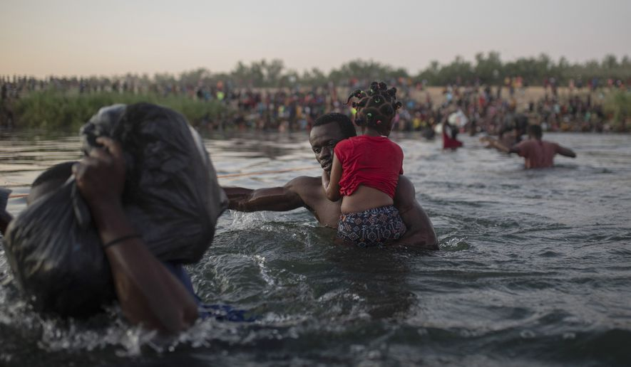 Haitian migrants wade across the Rio Grande from Del Rio, Texas, to Ciudad Acuña, Mexico, Sunday, Sept. 19, 2021, to avoid deportation to Haiti from the U.S. The U.S. is flying Haitians camped in a Texas border town back to their homeland and blocking others from crossing the border from Mexico in a massive show of force that signals the beginning of what could be one of America's swiftest, large-scale expulsions of migrants or refugees in decades. (AP Photo/Felix Marquez)