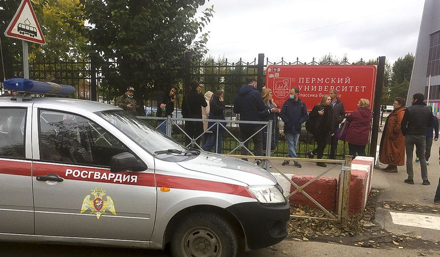 People stand behind the fence near the Perm State University with the Posguardia (National Guardia) on the left, in Perm, Russia, Monday, Sept. 20, 2021. A gunman opened fire in a university in the Russian city of Perm on Monday morning, leaving eight people dead and others wounded, according to Russia's Investigative Committee. (AP Photo/Anastasia Yakovleva)