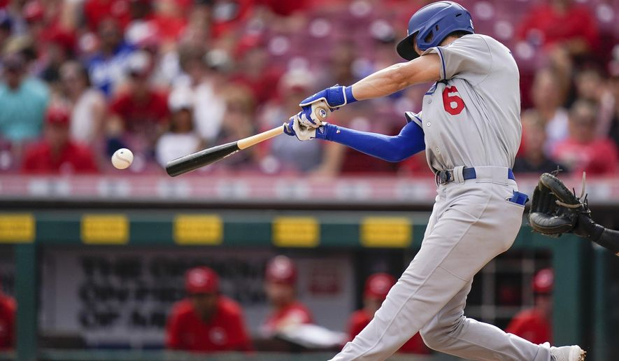 Los Angeles Dodgers' Trea Turner (6) hits a base hit during the ninth inning of a baseball game against the Cincinnati Reds in Cincinnati, Sunday, Sept 19, 2021. (AP Photo/Bryan Woolston) **FILE**