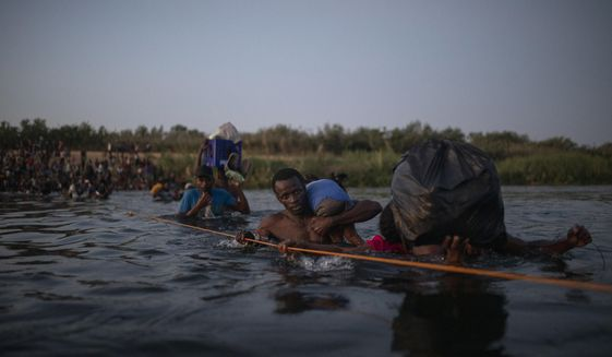 Migrants, many from Haiti, wade across the Rio Grande from Del Rio, Texas, to return to Ciudad Acuña, Mexico, late Sunday, Sept. 19, 2021, to avoid deportation to Haiti from the U.S.  The U.S. is flying Haitians camped in a Texas border town back to their homeland and blocking others from crossing the border from Mexico in a massive show of force that signals the beginning of what could be one of America's swiftest, large-scale expulsions of migrants or refugees in decades. (AP Photo/Felix Marquez)