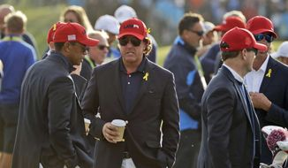 In this Sept. 30, 2018, file photo, Tiger Woods, left, and Phil Mickelson wait for the closing ceremony after Europe won the Ryder Cup on the final day of the 42nd Ryder Cup at Le Golf National in Saint-Quentin-en-Yvelines, outside Paris, France. Woods will be missng from the upcoming Ryder Cup, while Mickelson will serve as a vice-captain on the team. The pandemic-delayed 2020 Ryder Cup returns the United States next week at Whistling Straits along the Wisconsin shores of Lake Michigan.  (AP Photo/Matt Dunha, File) **FILE**