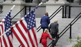 Britain's Prime Minister Boris Johnson arrives to meet Vice President Kamala Harris, Tuesday, Sept. 21, 2021, at the Eisenhower Executive Office Building on the White House campus in Washington. British Foreign Secretary Elizabeth Mary Truss is at left in red. (AP Photo/Alex Brandon)