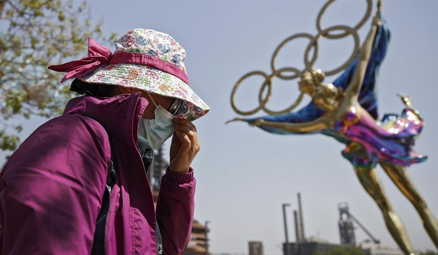 """FILE - In this May 2, 2021, file photo, a woman adjusts her face mask as she walks by a statue featuring the Beijing Winter Olympics figure skating on display at the Shougang Park in Beijing. China's """"zero tolerance"""" strategy of trying to isolate every case and stop transmission of the coronavirus has kept kept the country where the virus first was detected in late 2019 largely free of the disease. (AP Photo/Andy Wong, File)"""
