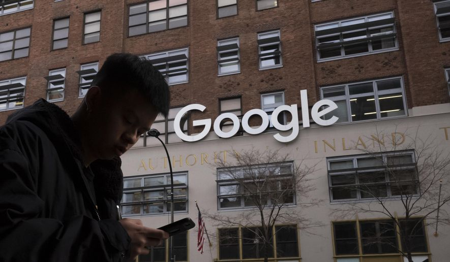 In this file photo dated Monday, Dec. 17, 2018, a man using a mobile phone walks past Google offices in New York. Google is planning to buy New York's St.  John's Terminal for $2.1 billion, making it the anchor of its Hudson Square campus. Alphabet and Google Chief Financial Officer Ruth Porat said Tuesday, Sept. 21, 2021,  that the company is looking to invest more than $250 million in its New York campus this year. (AP Photo/Mark Lennihan)  **FILE**