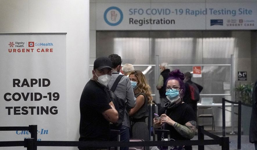 In this Oct. 15, 2020, file photo, United Airlines passengers wait in line to register at the SFO COVID-19 rapid testing site at San Francisco International Airport in San Francisco. San Francisco is requiring all workers at San Francisco International Airport to get vaccinated against COVID-19. Employees who are exempt must undergo weekly testing. The mandate announced Tuesday, Sept. 21, 2021, applies to roughly 46,000 on-site personnel, including employees of contractors and retail tenants. (AP Photo/Jeff Chiu, File)