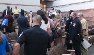 People confront police and security officers over an indoor face mask mandate during a commission meeting at the Clark County Government Center Tuesday, Sept. 21, 2021. (Ricardo Torres-Cortez/Las Vegas Sun via AP) **FILE**
