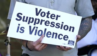 FILE - In this Monday, April 19, 2021, file photo, a former felon holds a sign addressing voter suppression during a Poor People's Campaign assembly in downtown Jackson, Miss. The demonstrator was among speakers who called for an initiative to try simplify the way Mississippi restores voting rights to people convicted of some felonies, and other social issues. On Wednesday, Sept. 22, 2021, a federal appeals court considered a lawsuit that seeks to overturn Mississippis ban on voting rights for people convicted of some felonies. (AP Photo/Rogelio V. Solis, File)