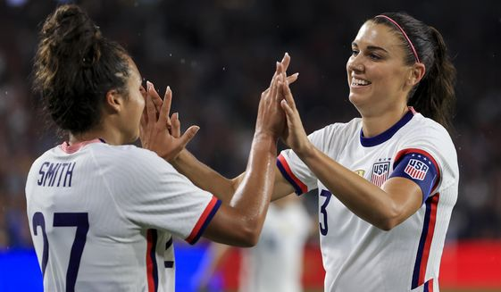 United States forward Alex Morgan, right, high-fives Sophia Smith after scoring a goal during the second half of an international friendly soccer match against Paraguay, Tuesday, Sept. 21, 2021, in Cincinnati. The United States won 8-0. (AP Photo/Aaron Doster) **FILE**
