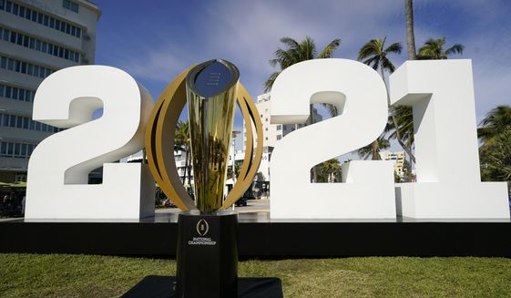 In this Jan. 7, 2021, file photo, the trophy for the College Football Playoff championship NCAA college football game is displayed along Ocean Drive, in Miami Beach, Fla. The College Football Playoff management committee is scheduled to meet Wednesday, Sept. 22, 2021, to discuss the feedback members have received from campuses since a 12-team expansion plan was unveiled in June. (AP Photo/Lynne Sladky, File) **FILE**