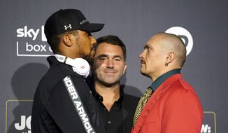 British boxer Anthony Joshua, left,  poses for a photo with Ukrainian boxer Oleksandr Usyk, right, with Chairman of Matchroom Boxing Eddie Hearn at centre, during a press conference at the Tottenham Hotspur Stadium, in London, Thursday, Sept. 23, 2021. Joshua faces Oleksandr Usyk in the second defense of his second spell as world heavyweight champion. Joshua holds the IBF, WBA and WBO belts and had been hoping to fight WBC champion Tyson Fury in an effort to become the undisputed heavyweight champ. Fury has to fight Deontay Wilder instead so Usyk is a replacement. (Zac Goodwin/PA via AP)
